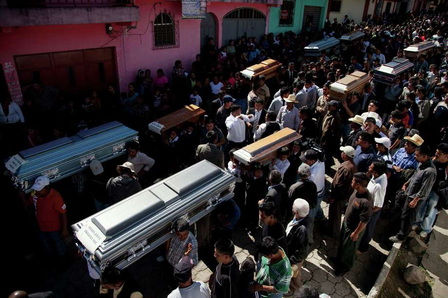 People carry the coffins with the remains of 10 members of the Vasquez family who died when an earthquake struck San Cristobal Cucho, Guatemala, Friday, Nov. 9, 2012. The family died when a magnitude 7.4 earthquake struck on Wednesday, collapsing their home and burying them alive, including a 4-year-old child, in the rubble. The powerful quake killed at least 52 people and left dozens more missing. Photo: Moises Castillo, Associated Press / AP