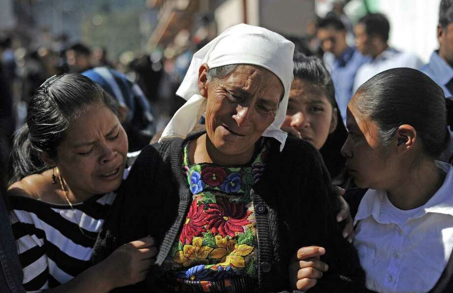 Two women comfort an elderly lady during the burial of ten victims of the earthquake --all members of the Vasquez family-- in San Cristobal Cucho municipality, in San Marcos, 260 km from Guatemala City, on November 9, 2012. A 7.4-magnitude earthquake rocked southwestern Guatemala on November 7, leaving 52 people dead, another 155 injured and 22 disappeared. The earthquake also rattled nerves in neighboring Mexico and El Salvador, sparking a tsunami alert on the Salvadoran coast and evacuations from offices, homes and schools as far north as Mexico City. Photo: JOHAN ORDONEZ, AFP/Getty Images / AFP