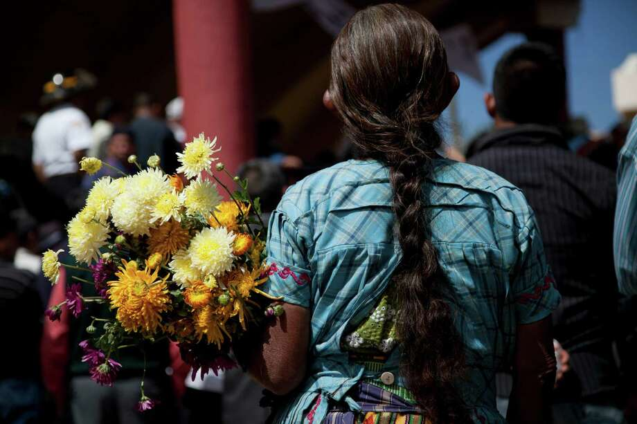 Berta Miguelina Miranda holds flowers during the funeral procession for Vasquez family who died when an earthquake struck San Cristobal Cucho, Guatemala, Friday, Nov. 9, 2012. Ten members of the family died Wednesday during the magnitude 7.4 earthquake that collapsed their home and buried them, including a 4-year-old child, in the rubble. The powerful quake killed at least 52 people and left dozens more missing. Photo: Moises Castillo, Associated Press / AP