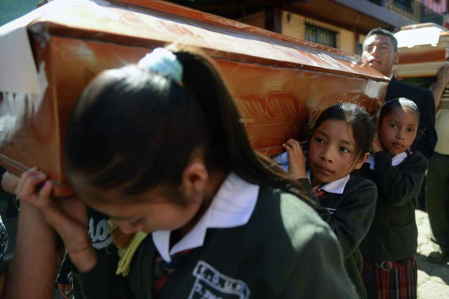 A group of schoolgirls carry a coffin during the burial of seven victims of the earthquake, in San Cristobal Cucho municipality, in San Marcos, 260 km from Guatemala City, on November 9, 2012. A 7.4-magnitude earthquake rocked southwestern Guatemala on November 7, killing 48 people and injuring another 150 while more were missing as homes crumbled. The earthquake also rattled nerves in neighboring Mexico and El Salvador, sparking a tsunami alert on the Salvadoran coast and evacuations from offices, homes and schools as far north as Mexico City. Photo: JOHAN ORDONEZ, AFP/Getty Images / AFP