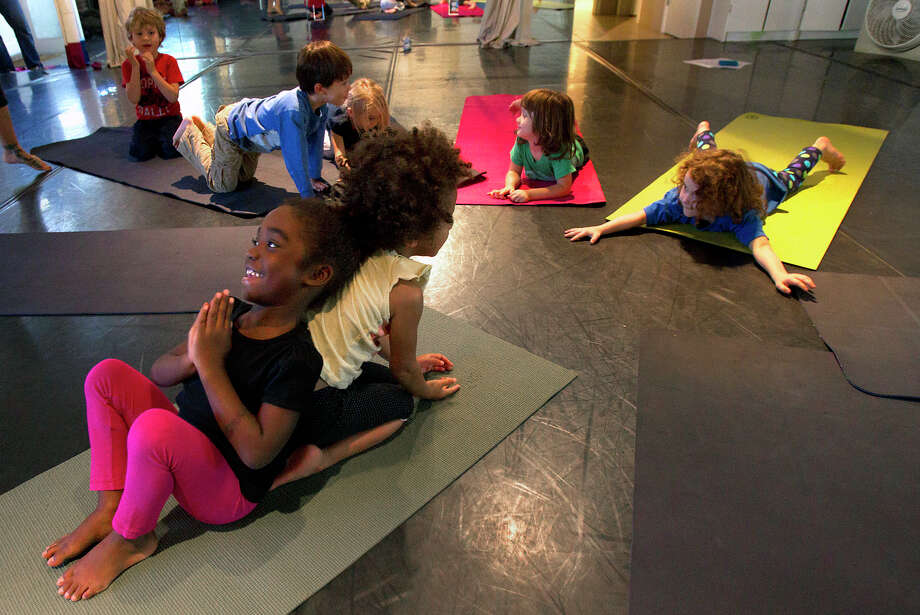 Lotis Wagner, 4, left, does the spinal stretch of the Lizard On A Rock pose with the assistance of Phania Vayner, 4, during HopeStone Kids' Yoga Friday, Nov. 9, 2012, in Houston. HopeStone aims to help youth become more conscious of themselves and their bodies through yoga. Photo: Cody Duty, Houston Chronicle / © 2012 Houston Chronicle