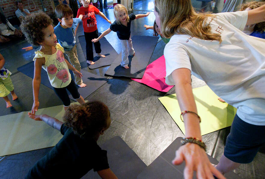 Katy Collins, right, teaches balance during Airplane pose at HopeStone Kids' Yoga Friday, Nov. 9, 20
