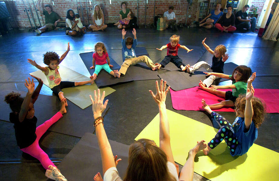 Katy Collins, bottom, unites kids in Flower Petal pose at HopeStone Kids' Yoga Friday, Nov. 9, 2012, in Houston. Photo: Cody Duty, Houston Chronicle / © 2012 Houston Chronicle