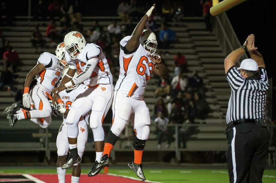 La Porte defensive lineman Corey Lee (63) celebrates with defensive end Alex Jones (42) and defensive back Ellis Hutchinson (2) after blocking a punt by Port Arthur Memorial's Tayylor Labrie in the end zone for a safety during the first quarter of a high school football game at Memorial Stadium, Friday, Nov. 9, 2012, in Port Arthur. Photo: Smiley N. Pool, Houston Chronicle / © 2012  Houston Chronicle