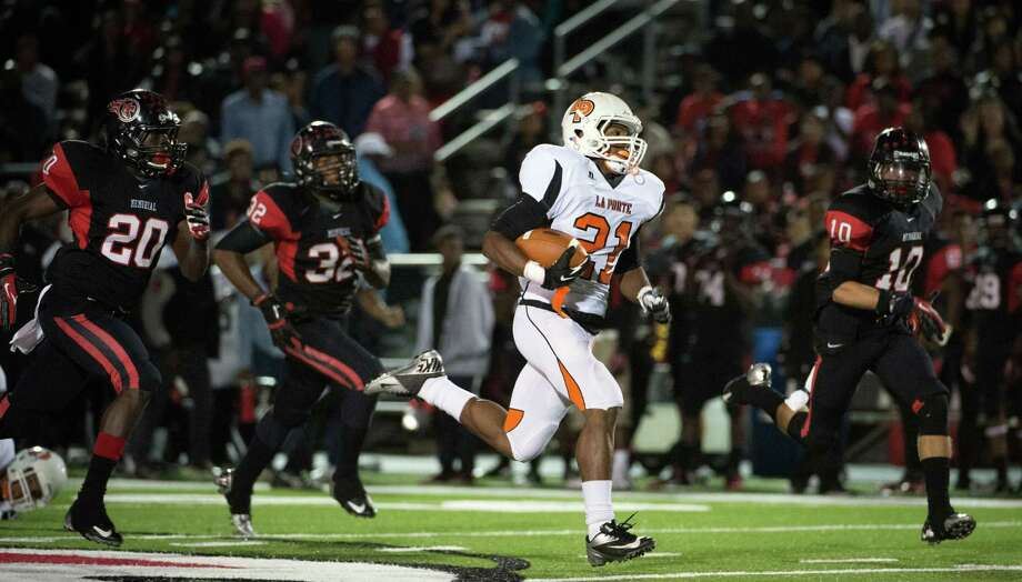 La Porte running back Keith Whitely (21) races past Port Arthur Memorial defensive back Devin Cockrell (20), linebacker Dante Lovilotte (32) and defensive back James Jenkins (10) as he goes 65 yards on the first offensive play of a high school football game at Memorial Stadium, Friday, Nov. 9, 2012, in Port Arthur. Photo: Smiley N. Pool, Houston Chronicle / © 2012  Houston Chronicle