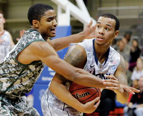 Connecticut guard Shabazz Napier, right, and Michigan State guard Gary Harris challenge for the ball during their NCAA men's basketball game on Saturday, Nov. 10, 2012, on the Ramstein U.S. Air Force Base, in Ramstein, Germany.  (AP Photo/Michael Probst) Photo: Michael Probst, Associated Press / Associated Press