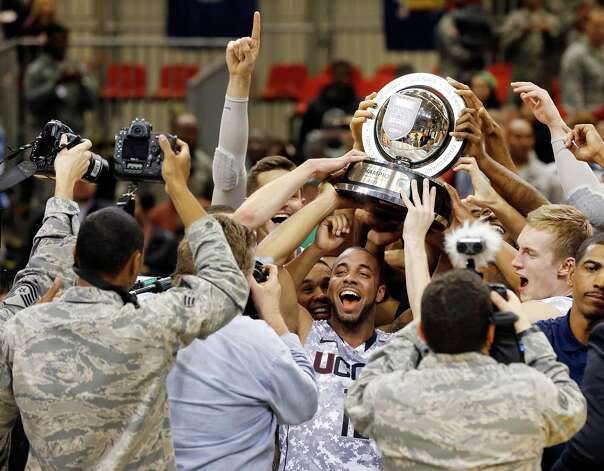 Connecticut guard R.J. Evans, center, holds up the trophy after beating Michigan State in their NCAA men's basketball game on Saturday, Nov. 10, 2012, on the Ramstein U.S. Air Force Base, in Ramstein, Germany.  (AP Photo/Michael Probst) Photo: Michael Probst, Associated Press / Associated Press