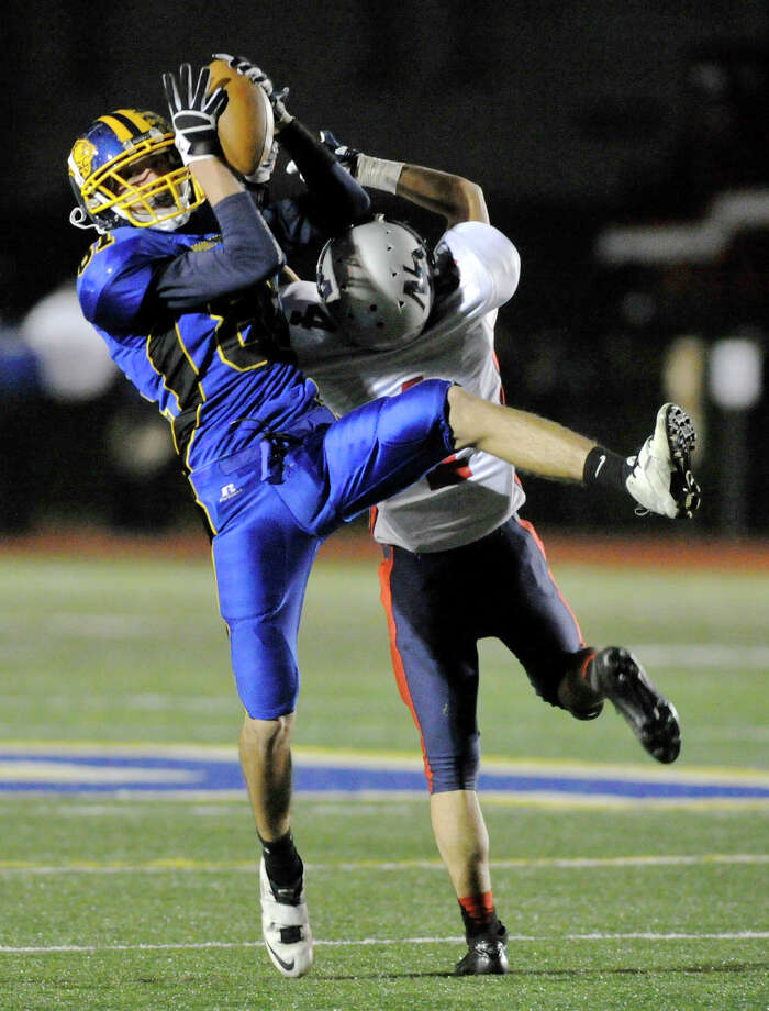Brookfield's Joe Redd catches the ball while under pressure from New Fairfield's Joey Hicks during their game at Brookfield High School on Friday, Nov. 9, 2012. New Fairfield won, 34-19. Photo: Jason Rearick / The News-Times