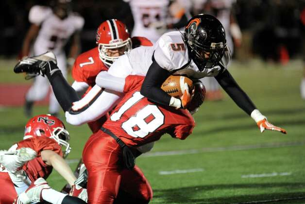 Stamford's Cameron Webb dives in an attempt to gain yards as he is tackled by New Canaan's Casey Oullette during Friday's football game at New Canaan High School on November 9, 2012. Photo: Lindsay Niegelberg / Stamford Advocate