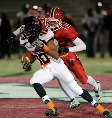 Stamford's John Pasard carries the ball as he is followed by New Canaan's John Rhudy during Friday's football game at New Canaan High School on November 9, 2012. Photo: Lindsay Niegelberg / Stamford Advocate