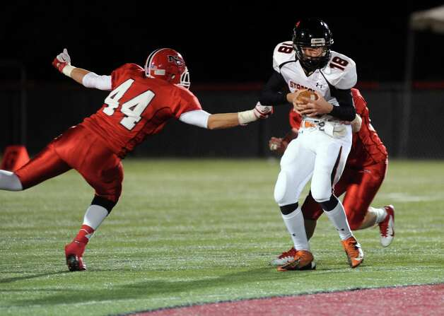 Stamford's Tyler Kane carries the ball as New Canaan's Zach Allen, left, reaches to tackle during Friday's football game at New Canaan High School on November 9, 2012. Photo: Lindsay Niegelberg / Stamford Advocate
