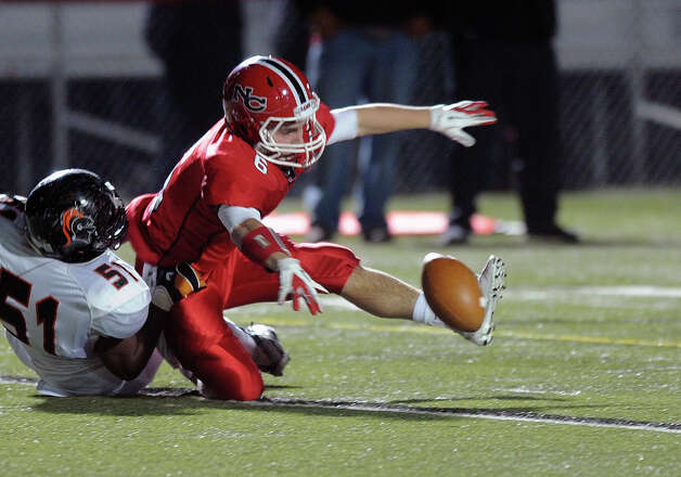 New Canaan's Teddy Bossidy reaches for the ball after he dropped it while being tackled by Stamford's Darren Philips during Friday's football game at New Canaan High School on November 9, 2012. Photo: Lindsay Niegelberg / Stamford Advocate