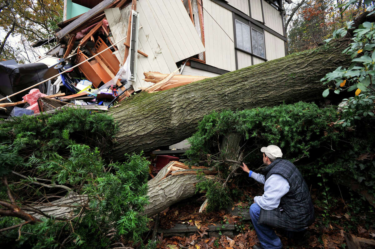 Reynaldo Lopez surveys the damage to his family's home in Danbury on Wednesday, Oct. 31, 2012. The house sustained the damage due to a large tree falling on it Monday evening because of storm Sandy.