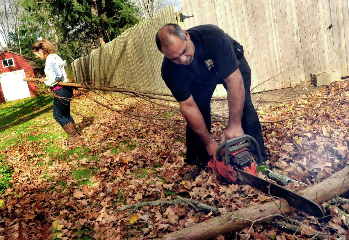 Sophia Chiravelli helps her dad, Jim, cut brush that fell during Hurricane Sandy in Newtown. Photographed Friday, Nov. 2, 2012.