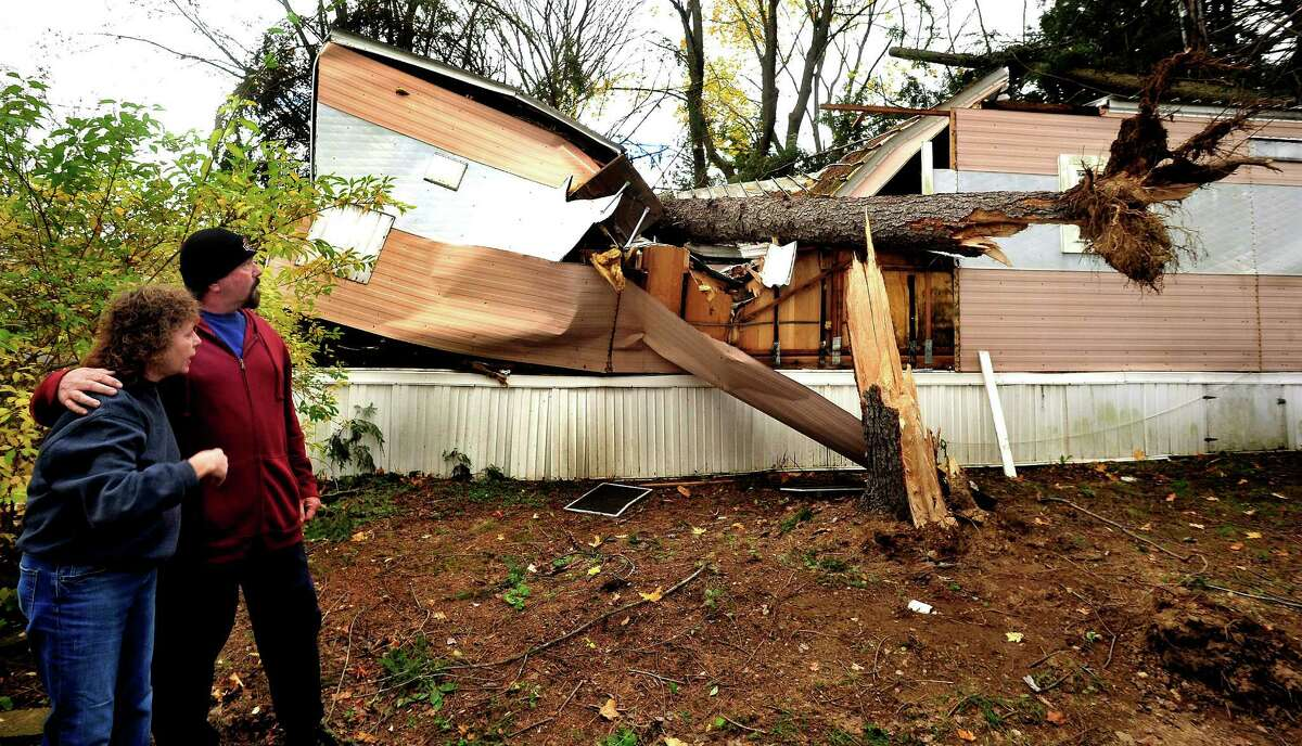 Kathleen Wade and Bill McLean look at her crushed mobile home. McLean pulled Wade from the home after two trees fell on it during Hurricane Sandy in Newtown. Photographed Friday, Nov. 2, 2012.