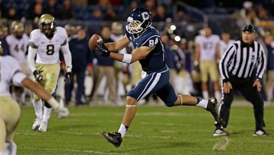 Former Connecticut tight end Ryan Griffin (94) hauls in a pass against Pittsburgh during the first half of an NCAA college football game in East Hartford, Conn., Friday, Nov. 9, 2012. The Huskies are looking for someone -- anyone -- to fill his and John Delahunt's position. (AP Photo/Charles Krupa)