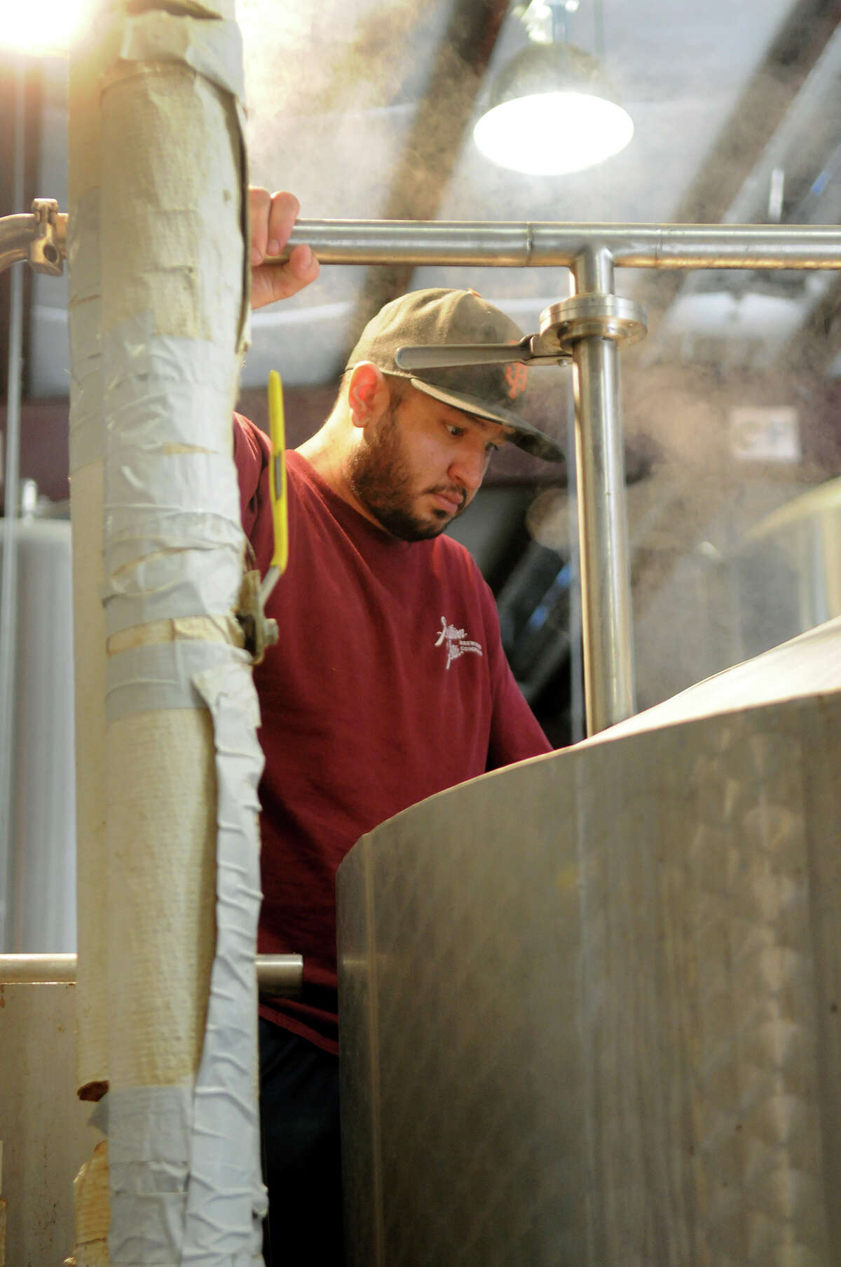 Jason Gutierrez monitors a brew kettle during a beer cooking session at the Southern Star Brewery.
