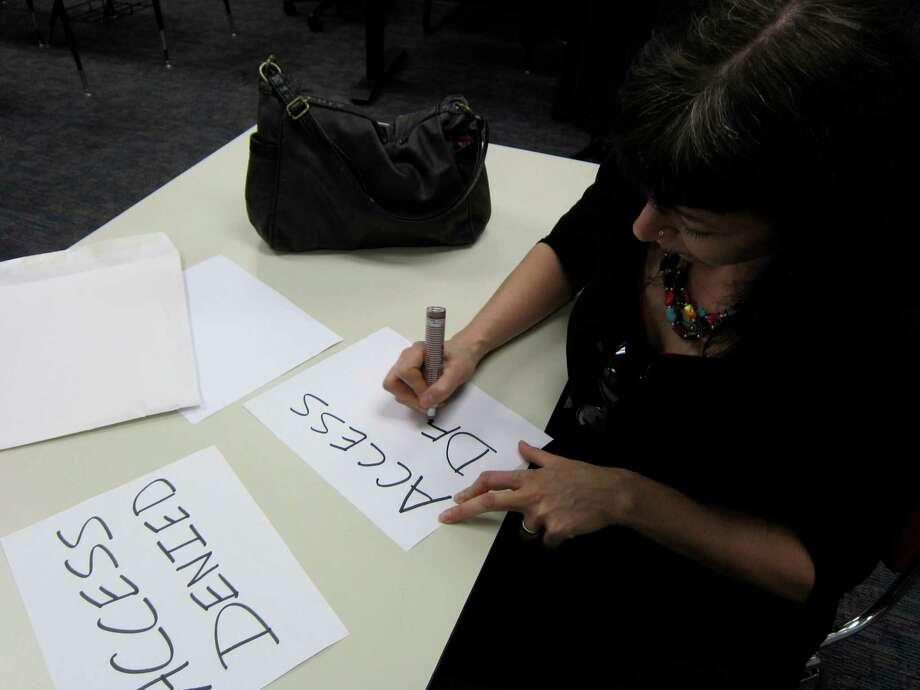 Kathleen Kupelian, state representative of the American Federation of Teachers in Texas, makes signs to let students, faculty and staff know that school officials caused the cancellation of a presentation on civil rights by a federal official.