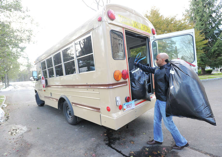 Johnny Montanez, faculty director of the Brunswick School Community Service Club, loads donated clothes into a Brunswick School bus from the  Neighbor to Neighbor pantry in Greenwich, Friday afternoon, November 9, 2012. Montanez said the clothing donations will be distributed to victims of Hurricane Sandy in New York City. Neighbor to Neighbor is a community service organization that distributes clothes, food and other necessities to those in need. Photo: Bob Luckey / Greenwich Time