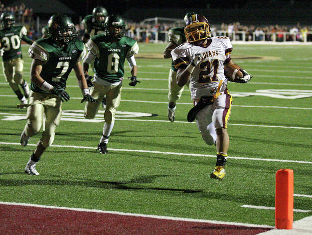 Harlandale's Nicholas Martinez heads to the end zone for a touchdown ahead of McCollum defenders during double overtime action of the Frontier Bowl Friday Nov. 9, 2012 at Harlandale Memorial Stadium. Harlandale won in double overtime 43-36. Photo: Edward A. Ornelas, Express-News / © 2012 San Antonio Express-News