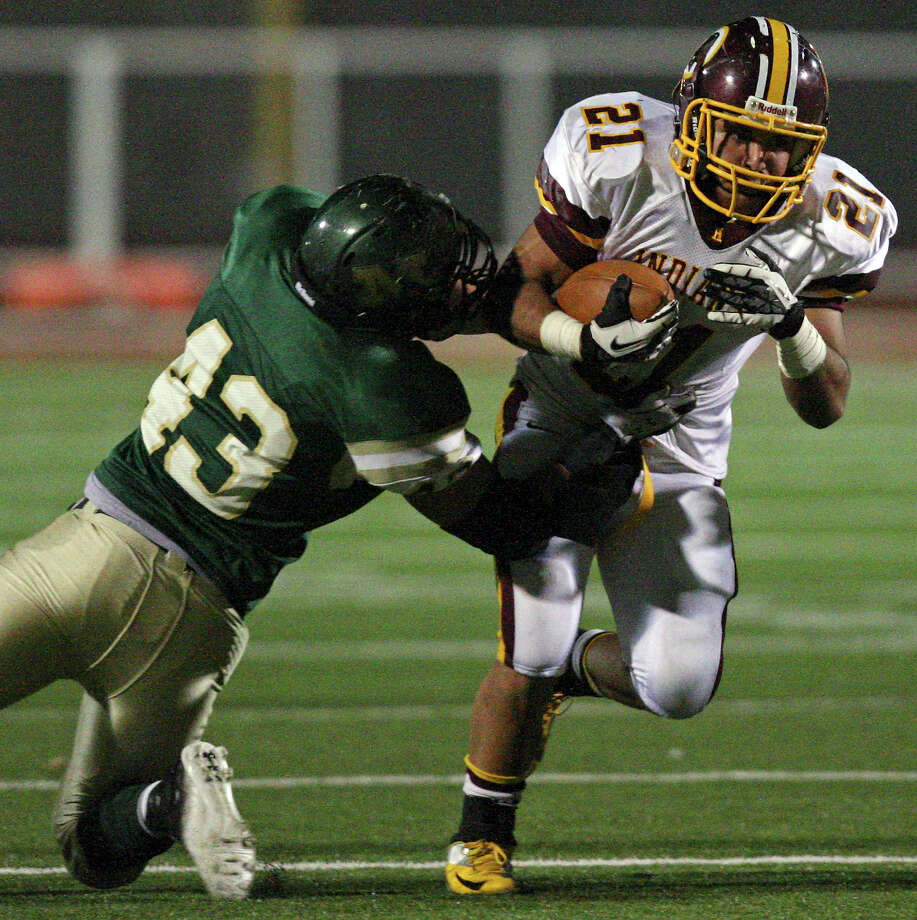Harlandale's Nicholas Martinez tries to shake the tackle of McCollum's Shawn Murray during first half action of the Frontier Bowl Friday Nov. 9, 2012 at Harlandale Memorial Stadium. Photo: Edward A. Ornelas, Express-News / © 2012 San Antonio Express-News