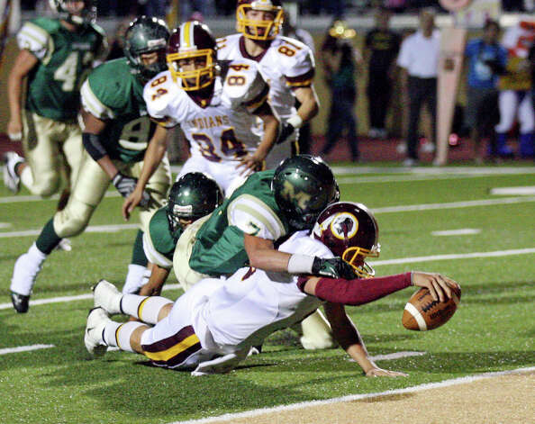 Harlandale's Brandon Ramon stretches for a touchdown ahead of McCollum's Conrad Garcia during first half action of the Frontier Bowl Friday Nov. 9, 2012 at Harlandale Memorial Stadium. Photo: Edward A. Ornelas, Express-News / © 2012 San Antonio Express-News
