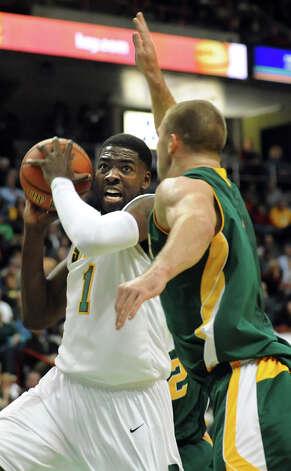Siena's O.D. Anosike (1), left, grabs the rebound as Vermont's Brian Voelkel (1) defends during their basketball game on Friday, Nov. 9, 2012, at Times Union Center in Albany, N.Y. (Cindy Schultz / Times Union) Photo: Cindy Schultz / 00019962A