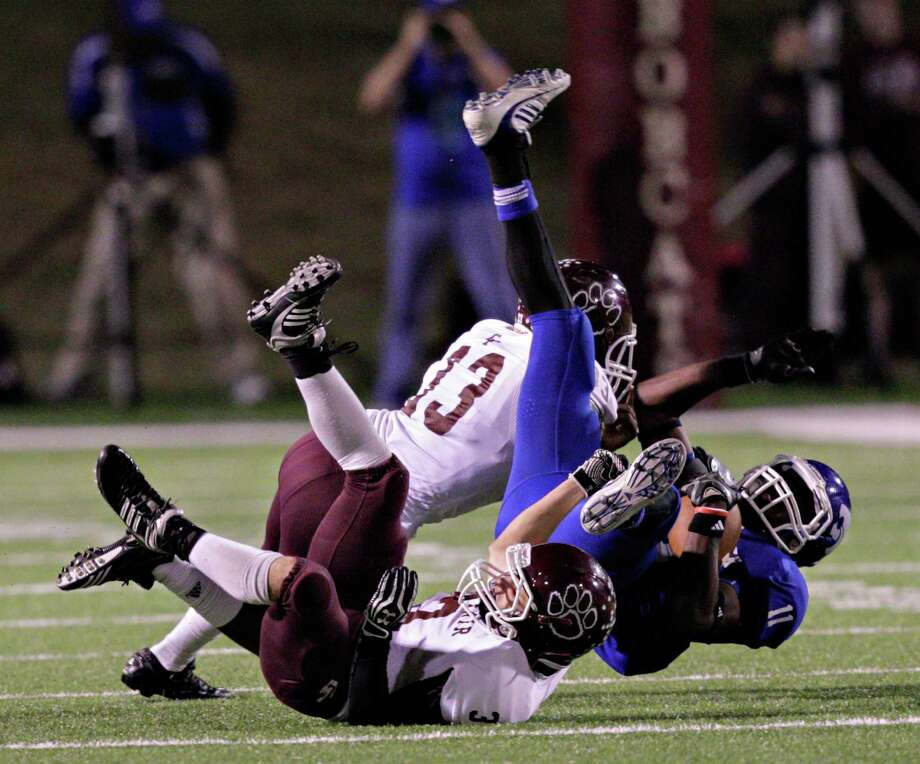 Cy Creek's Bobby Chan-Chan (11) holds on to a pass as he is hit by Cy-Fair's Ryan Oakes (3) during Cy-Fair's playoff-clinching victory Friday night at Pridgeon Stadium. Photo: Bob Levey, For The Chronicle / ©2012 Bob Levey