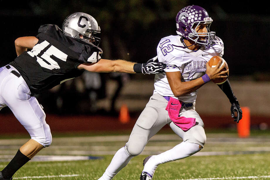 Warren quarterback Jordan Sneed (right) tries to escape the grasp of Clark's Zach Wood during the first quarter of their game at Farris Stadium on Nov. 9, 2012.  Clark claimed a spot in the playoffs with a 27-26 overtime victory over the Warriors.  MARVIN PFEIFFER/ mpfeiffer@express-news.net Photo: MARVIN PFEIFFER, Express-News / Express-News 2012