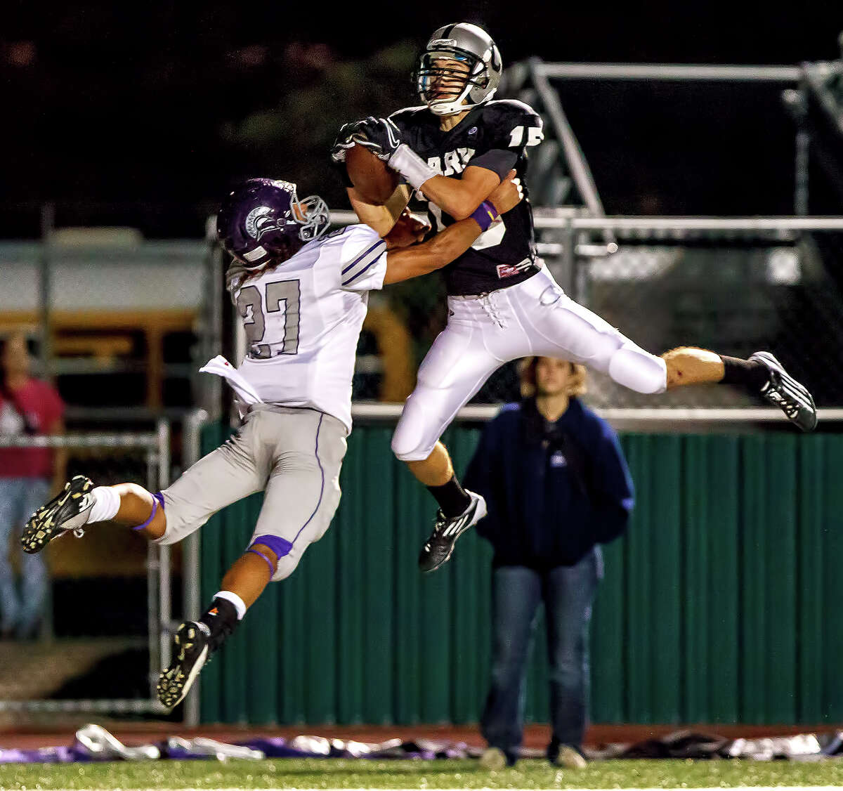 Clark's Presley Miller (right) leaps in the end zone for a 14-yard touchdown reception over Warren's Luis Mercer during the third quarter of their game at Farris Stadium on Nov. 9, 2012. Clark claimed a spot in the playoffs with a 27-26 overtime victory over the Warriors. MARVIN PFEIFFER/ mpfeiffer@express-news.net