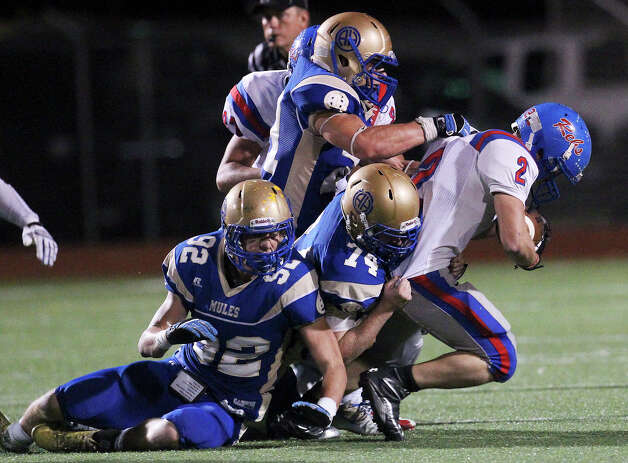 Alamo Heights defenders Blake Klumpp (92), Carter Poore (74) and Nick Uretsky (21) take down Buda Hays running back Marco Solis (02) during their game at Alamo Heights on Friday, Nov. 9, 2012. Buda Hays defeated Alamo Heights, 24-21. Photo: Kin Man Hui, Express-News / © 2012 San Antonio Express-News