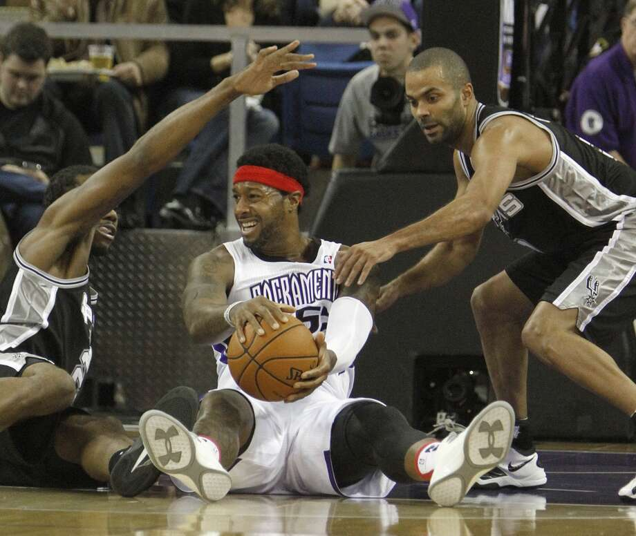 Sacramento Kings forward James Johnson, center, tries to protect the ball from San Antonio Spurs forward Kawhi Leonard, left, and Tony Parker during the first quarter of an NBA basketball game in Sacramento, Calif., Friday, Nov. 9, 2012. (AP Photo/Rich Pedroncelli) (Associated Press)