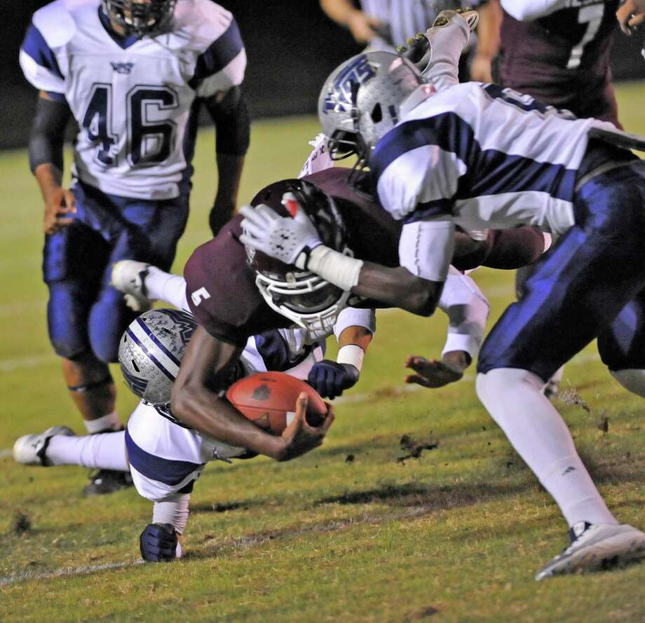 Tiger #5, Patrick Reed, center,  hangs onto the ball as he is taken down by Mustangs defenders.   The Silsbee High School Tigers hosted the West Orange-Stark High School Mustangs Friday night November 9, 2012 at Tiger stadium in Silsbee. This is a District 21-3A game, and both teams were undefeated in district play going into the game. At the half, the Mustangs are up 13-12.	 Dave Ryan/The Enterprise Photo: Dave Ryan
