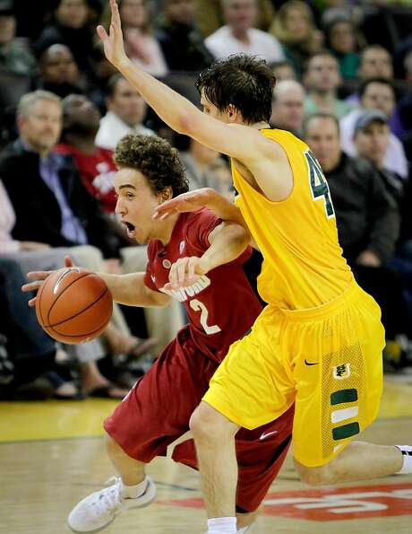 Stanford's Aaron Bright drives against USF's Cody Doolin at Oracle Arena in the season opener for bo