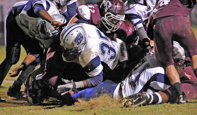 Mustang #35, Abear Simien, center, can't be stopped by a host of Tiger defenders as he breaks through to score a touchdown for the Mustangs.  The Silsbee High School Tigers hosted the West Orange-Stark High School Mustangs Friday night November 9, 2012 at Tiger stadium in Silsbee. This is a District 21-3A game, and both teams were undefeated in district play going into the game. At the half, the Mustangs are up 13-12.	 Dave Ryan/The Enterprise Photo: Dave Ryan