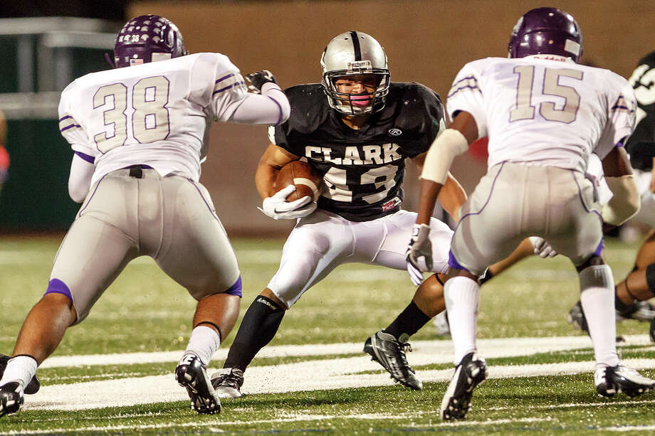 Clark's Branden Valle (center) tries to find a way past Warren's Rey Salazar (left) and  Tamarian Torns during the second quarter of their game at Farris Stadium on Nov. 9, 2012.  Clark claimed a spot in the playoffs with a 27-26 overtime victory over the Warriors.  MARVIN PFEIFFER/ mpfeiffer@express-news.net Photo: MARVIN PFEIFFER, Express-News / Express-News 2012