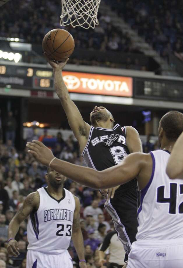San Antonio Spurs guard Patty Mills, center, drives to the basket between Sacramento Kings Marcus Thornton, left, and Chuck Hayes during third quarter of an NBA basketball game in Sacramento, Calif., Friday, Nov. 9, 2012.  The Spurs won 97-86.(AP Photo/Rich Pedroncelli) (Associated Press)
