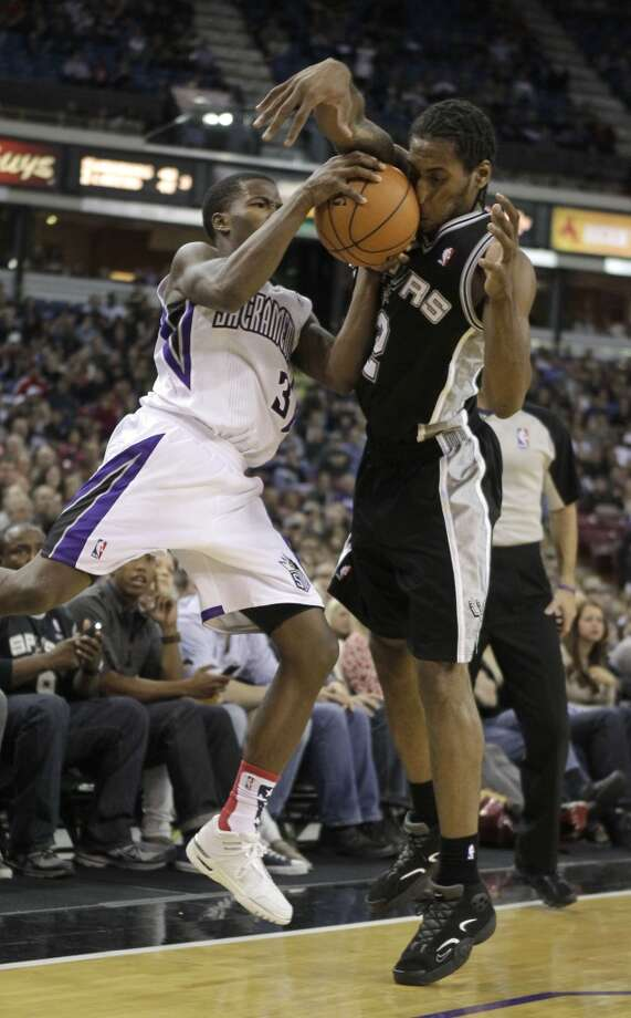 Sacramento Kings guard Aaron Brooks, left, and San Antonio Spurs forward Kawhi Leonard collide as they go for the ball during fourth quarter of an NBA basketball game in Sacramento, Calif., Friday, Nov. 9, 2012.  The Spurs won 97-86.(AP Photo/Rich Pedroncelli) (Associated Press)