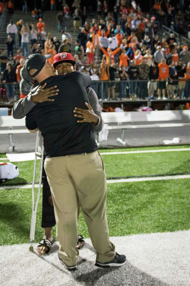 La Porte running back Keith Whitely, who was injured earlier in the game and came back using crutches, gets a hug from a coach during final moments of the Bulldogs victory over Port Arthur Memorial in a high school football game at  Memorial Stadium, Friday, Nov. 9, 2012, in Port Arthur. Photo: Smiley N. Pool, Houston Chronicle / © 2012  Houston Chronicle