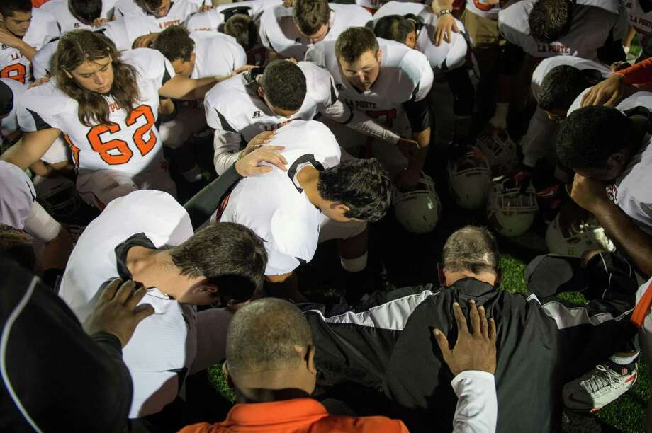La Porte players huddle around head coach Jeff Lareau in prayer following the Bulldogs victory over Port Arthur Memorial in a high school football game at  Memorial Stadium, Friday, Nov. 9, 2012, in Port Arthur. Photo: Smiley N. Pool, Houston Chronicle / © 2012  Houston Chronicle