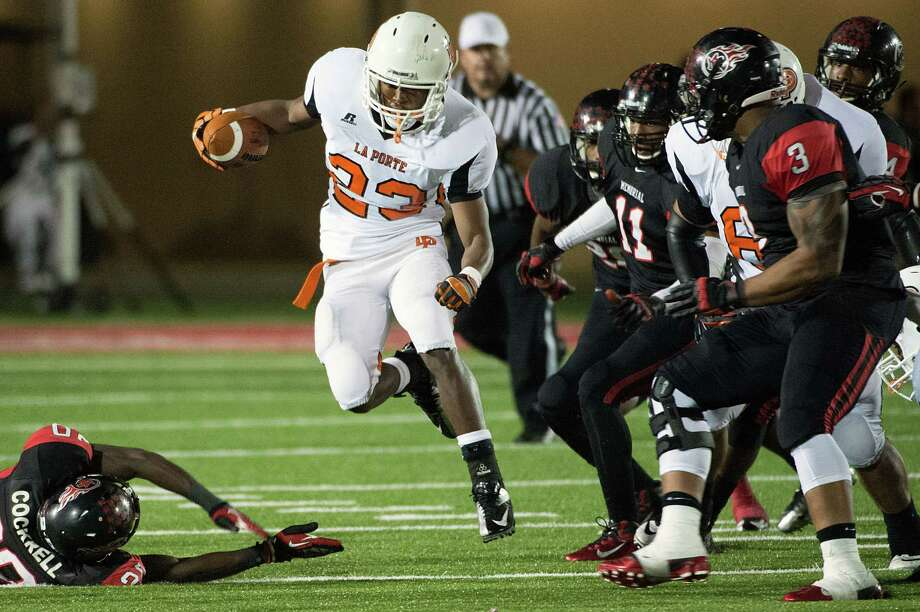 La Porte running back Johnathan Lewis (23) gets past Port Arthur Memorial defensive back Devin Cockrell (20) during the second half of a high school football game at  Memorial Stadium, Friday, Nov. 9, 2012, in Port Arthur. Photo: Smiley N. Pool, Houston Chronicle / © 2012  Houston Chronicle