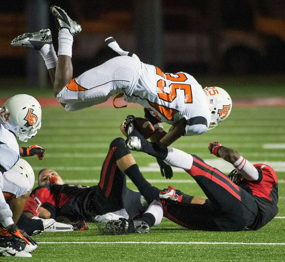 La Porte running back Clifton Figaro (25) fumbles the ball as he is upended by the Port Arthur Memorial defense during the second half of a high school football game at  Memorial Stadium, Friday, Nov. 9, 2012, in Port Arthur. La Porte retained possession. Photo: Smiley N. Pool, Houston Chronicle / © 2012  Houston Chronicle