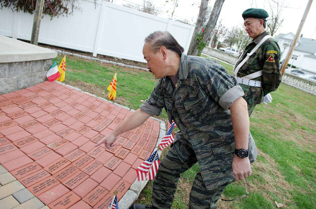 South Vietnamese Navy Veteran Qua Le, who served from 1968-1975, points to bricks at the Veterans Memorial as South Vietnamese Special Forces Veteran Ngoc Nguyen, who served from 1969-1975, looks on during the third annual Veterans Day Mass and Ceremony at St. Margaret Shrine on Park Ave. in Bridgeport on Saturday, Nov. 10, 2012. Participants in the ceremony included South Vietnamese Military Veterans, the Greater Bridgeport Detachment of the Marine Corps League, Port 5 Naval Veterans, and the Catholic War Veterans Post 1466. Photo: Amy Mortensen / Connecticut Post Freelance