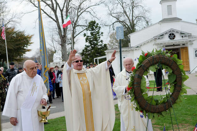 Fr. Alfonso Picone blesses the Memorial wreath during the third annual Veterans Day Mass and Ceremony at St. Margaret Shrine on Park Ave. in Bridgeport on Saturday, Nov. 10, 2012. Joining Fr. Picone are Deacon Joseph Melita and Fr. Artuso Grezioso. Participants in the ceremony included South Vietnamese Military Veterans, the Greater Bridgeport Detachment of the Marine Corps League, Port 5 Naval Veterans, and the Catholic War Veterans Post 1466. Photo: Amy Mortensen / Connecticut Post Freelance