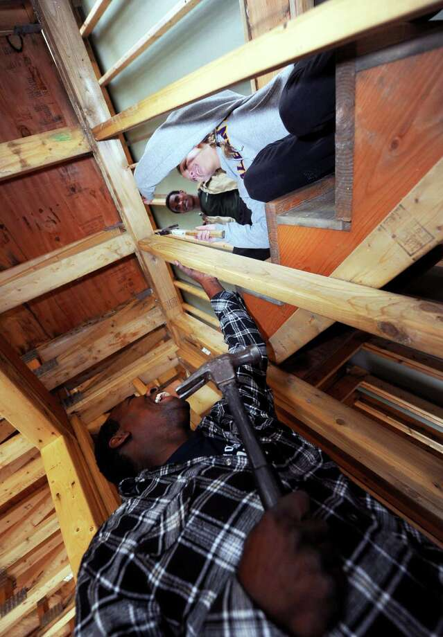 Site manager Alphonso Gavin,left, works with UAlbany student volunteers Collen Hulbert and Denzel Boudreaux on a Habitat for Humanity home in Albany, NY Friday Oct. 26, 2012. (Michael P. Farrell/Times Union) Photo: Michael P. Farrell / 00019811A