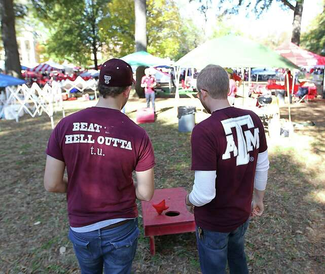 Collin Brewer, of Houston, left, and Justin Dalton, right, both Texas Aggie alums,  tailgate on the