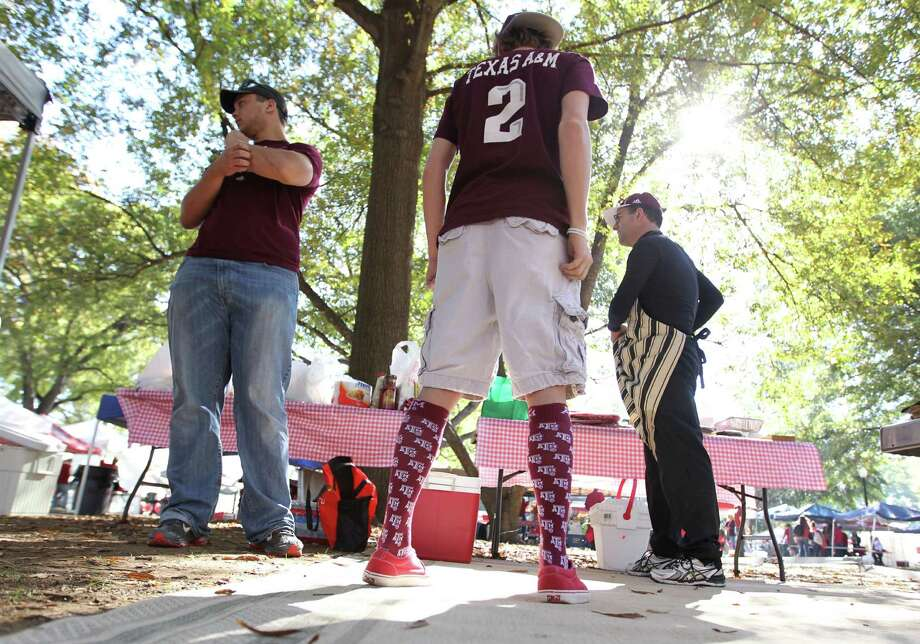 "Mitchell Long, a junior at A&M, left, tailgates on the ""quad"" with Brandon Neely, 17, of Waco, center, and Joe Calao, of Waco, before the start of a college football game at Bryant-Denny Stadium, Saturday, Nov. 10, 2012, in Tuscaloosa. Photo: Karen Warren, Houston Chronicle / © 2012  Houston Chronicle"