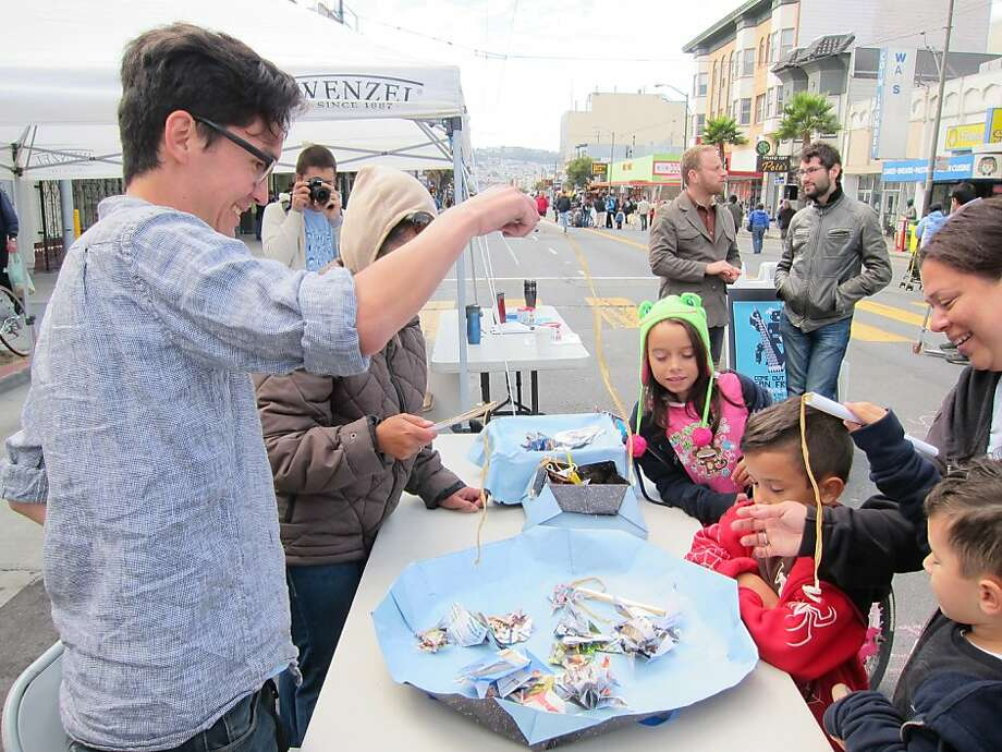 Adults and kids try their hand at origami fishing at a previous Come Out and Play, which started in New York City. Photo: Jackie Hasa