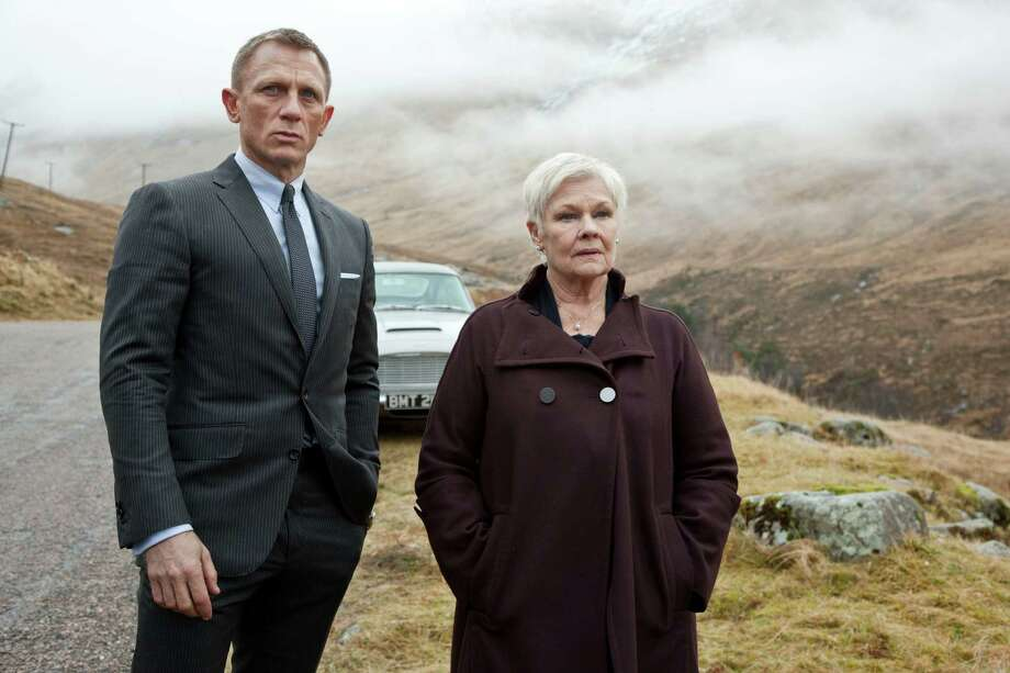 "This film image released by Sony Pictures shows Daniel Craig as James Bond, left, and Judi Dench as MI6 head M, in a scene from the film ""Skyfall."" Dench has been the Bond matriarch: the strong-willed, no-nonsense mainstay of feminine authority in a movie franchise that has, more often than not, featured slightly more superficial womanly traits. In ""Skyfall,"" Dench isn't just dictating orders from headquarters, but is thrown directly into the action when a former MI6 agent, played by Javier Bardem, is bent on revenge against her.   (AP Photo/Sony Pictures, Francois Duhamel) Photo: Francois Duhamel"