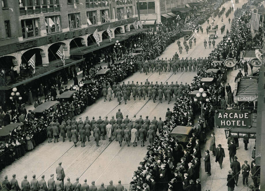 "The caption for this P-I photo read: ""Seattle soldiers marching up 2nd Ave. in March, 1919, on their return from the World War. Huge crowds lined the streets, bands played and it was a really gala occasion – for everyone except those who couldn't forget some loved ones who remained behind to sleep forever under foreign soil."" Photo: Seattlepi.com"